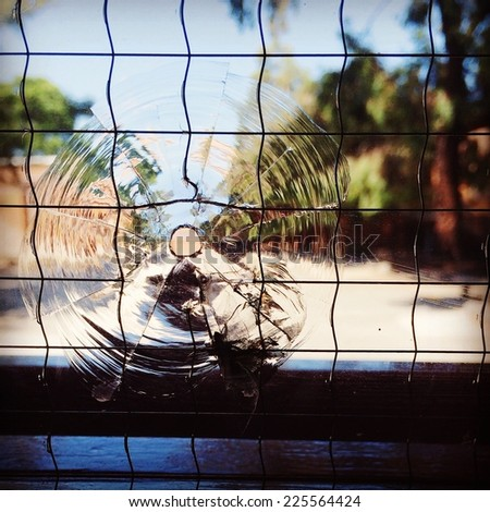 Wire covers a window with a round hole looking out onto a tree lined road. - stock photo