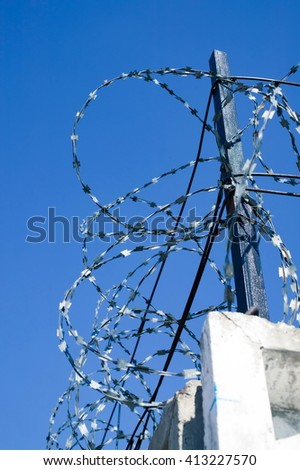 Wire entanglement on a concrete fence. Barbed wire. - stock photo