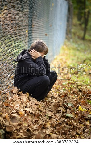 wire fence sitting in front of hooded young - stock photo