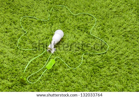 Wire flower plugged  to the earth. Energy saving lamp in the socket, with green wire, on the green carpet. - stock photo