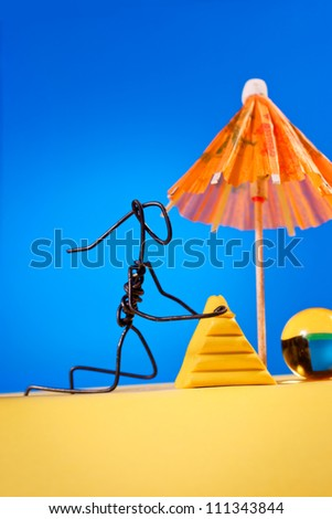 Wire girl building sand castle on the beach - stock photo