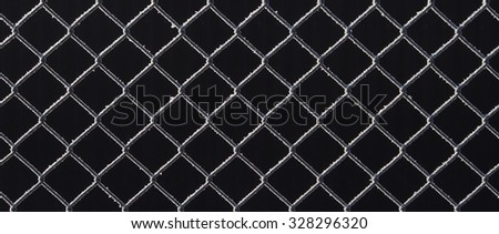 Wire netting fence covered with frost in wintertime - stock photo