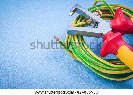 Wire stripper pliers electric cables on blue background electricity concept. - stock photo