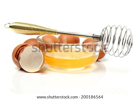 Wire whisk and brown eggs on white background
