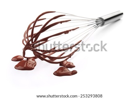 wire whisk with chocolate against white background - stock photo