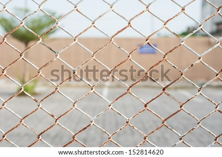 wired fence of car park - stock photo