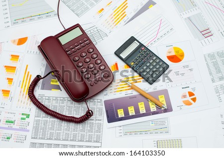 Wired telephone and scientific calculator on table - stock photo