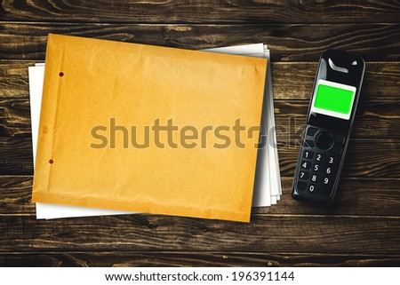 Wireless cordless phone and blank envelope with copy space on wooden tabletop, top view - stock photo