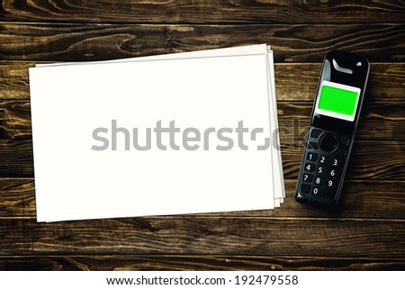 Wireless cordless phone and blank paper with copy space on wooden tabletop. - stock photo