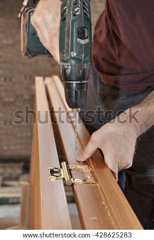 Wireless electric drill in the hands of a carpenter, drilling holes for fastening brass door hinges in wooden interior door, close-up.
