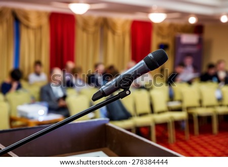 Wireless Microphone closeup in a hall at conference. People sitting at in the negotiations in the conference room - stock photo