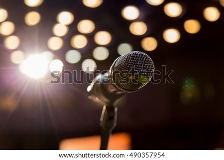 Wireless microphone on stage, blurred lights in the background