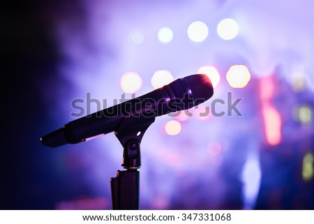Wireless microphone stand on the stage venue with blur bokeh background - stock photo
