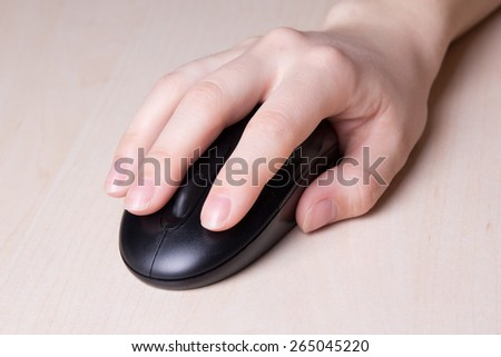 wireless mouse in female hand on wooden table - stock photo