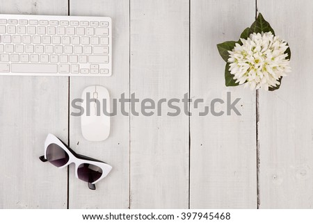 Wireless slim keyboard and mouse, glasses, flower on white wooden background - stock photo