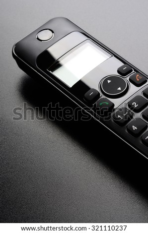 Wireless telephone on empty black grained table