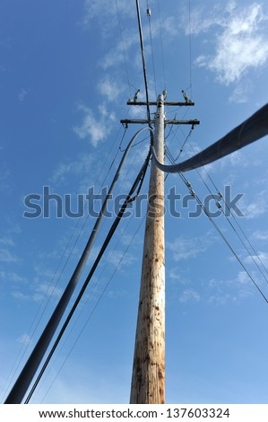 Wires and cables from a telephone pole come to the ground - stock photo