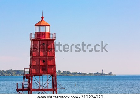 Wisconsin's red Racine North Breakwater Lighthouse, on Lake Michigan, is backed by the Wind Point Lighthouse on the horizon. Public outcry saved this light, now a symbol of the city, from demolition. - stock photo