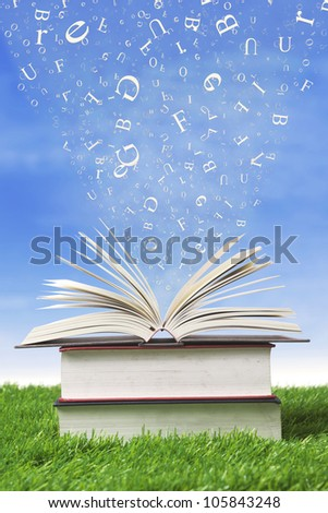 Wisdom books with letters falling into the pages, shot outdoor - stock photo