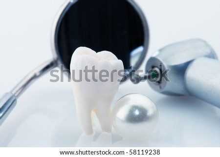 Wisdom tooth, natural pearl and dental tools. Healthy teeth concept. Blue tinted image - stock photo