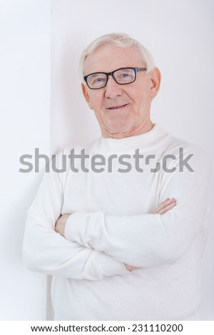 Wise and confidence. Confident senior man keeping arms crossed and smiling at camera while leaning at the wall - stock photo
