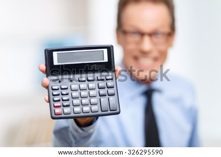 Wise device. Selective focus of calculator in hands of professional lawyer holding it and being involved in work - stock photo