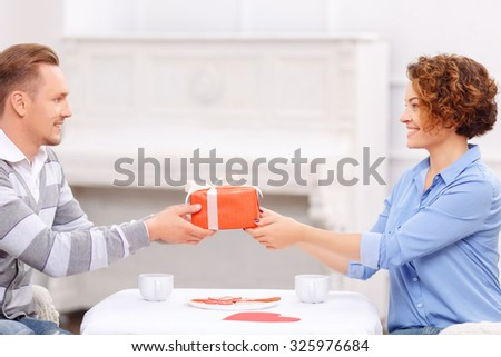 Wish you all the best. Overjoyed handsome man giving present to his girl friend sitting at the table and having dinner. - stock photo