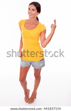 Wishing brunette woman gesturing crossed fingers while looking at camera and wearing a yellow t-shirt and short jeans isolated - stock photo