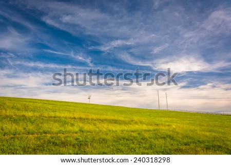 Wispy clouds over a grassy hill in York County, Pennsylvania. - stock photo