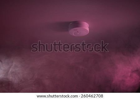 Wispy Smoke Around White Fire Sensor In House - stock photo