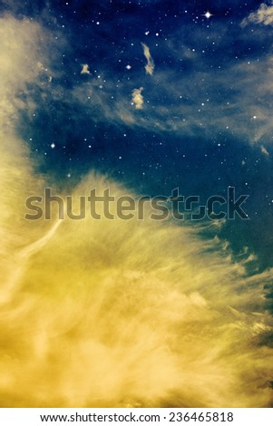 Wispy yellow cloud formations with stars at night.  Image displays a strong paper grain and texture at 100 percent. - stock photo