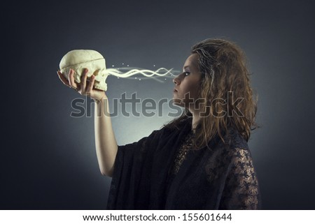 Witch casts a spell with a skull - stock photo