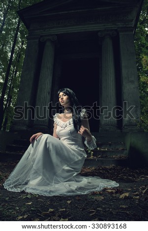 Witch from a crypt in the cemetery - stock photo