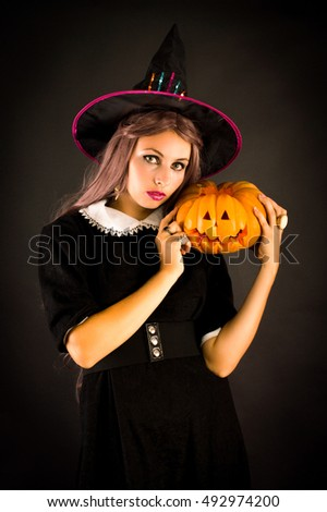 Witch in the hat and pumpkin. On a black background.