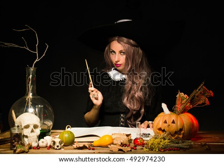 Witch in the hat at the table with a magic wand. On a black background.