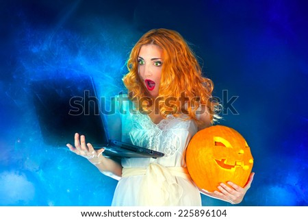 Witch with computer and Jack O' Lantern - stock photo