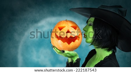 Witch with green skin kisses a Halloween pumpkin at midnight