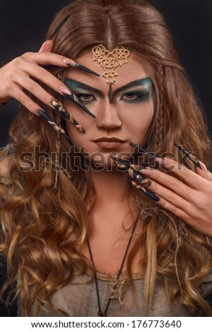witch with long nails with snakes - stock photo