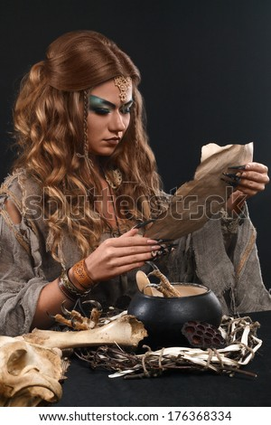 witch with papers with magic spells - stock photo