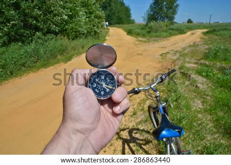 With a compass and a Bicycle front fork. Orientation during a bike ride in rural areas. - stock photo