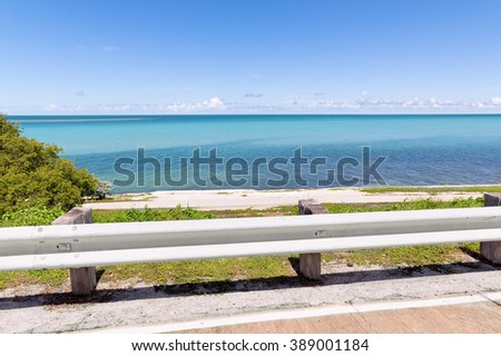 With a highway guardrail in the foreground, the warm tropical water sits over the horizon off one of the islands in the Florida Keys.