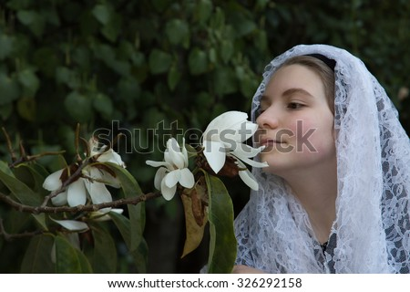 With a white lace veil, a young, innocent girl smells a freshly opened, white magnolia blossom. A stunning scene for fragrance and the first signs of spring. - stock photo