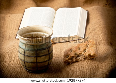 with chalice and bread on the textile tablecloth - stock photo