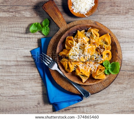 with chili peppers on a wooden table. Rustic style. filled pasta dish - stock photo