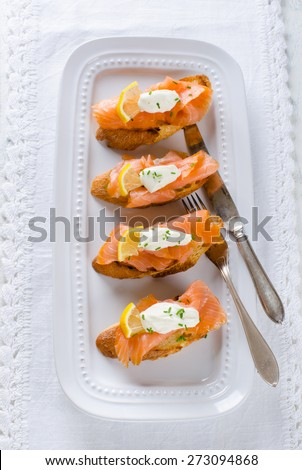 with cream fresh, lemon and chives on white plate - stock photo