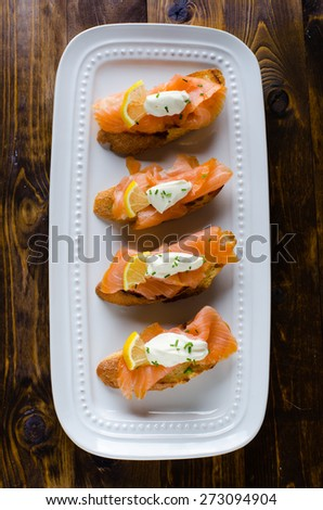 with cream fresh, lemon and chives on white plate on wooden background - stock photo