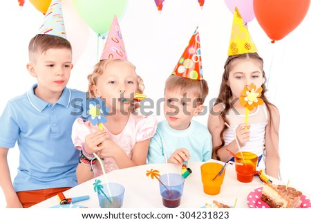With flowers. Two little boys and pair of beautiful girls playing with toy flowers at birthday party.