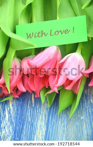 with love wishes and bouquet of gorgeous red tulips - stock photo