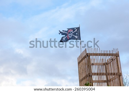 with some clouds there is a lookout with a pirate flag - stock photo
