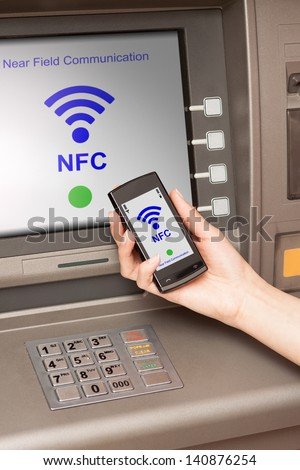 withdrawing money from atm with a mobile phone a NFC terminal - stock photo